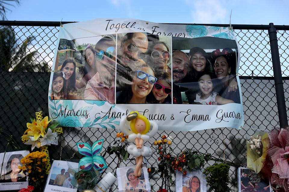 SURFSIDE, FLORIDA - JULY 15: A banner with pictures of a family hang in the memorial that has photographs of some of the victims from the partially collapsed 12-story Champlain Towers South condo building on July 15, 2021 in Surfside, Florida. 92 victims have been identified as the search and recovery effort nears completion.  (Photo by Joe Raedle/Getty Images)