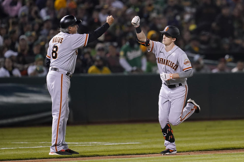 San Francisco Giants' Mike Yastrzemski, right, is congratulated by third base coach Ron Wotus after hitting a home run against the Oakland Athletics during the fifth inning of a baseball game in Oakland, Calif., Friday, Aug. 20, 2021. (AP Photo/Jeff Chiu)