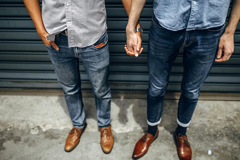 Homosexual couple holding hands outdoors in the city
