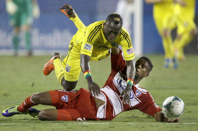 FC Dallas' Kellyn Acosta, right, takes out Columbus Crew's Dominic Oduro (11) during the first half of an MLS soccer game Sunday, Sept. 29, 2013, in Frisco, Texas. (AP Photo/LM Otero)