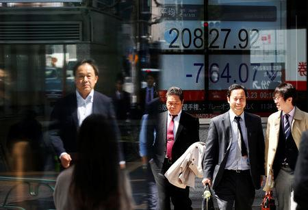 FILE PHOTO: People walk past an electronic board showing Japan's Nikkei average outside a brokerage in Tokyo, Japan, March 23, 2018.  REUTERS/Toru Hanai