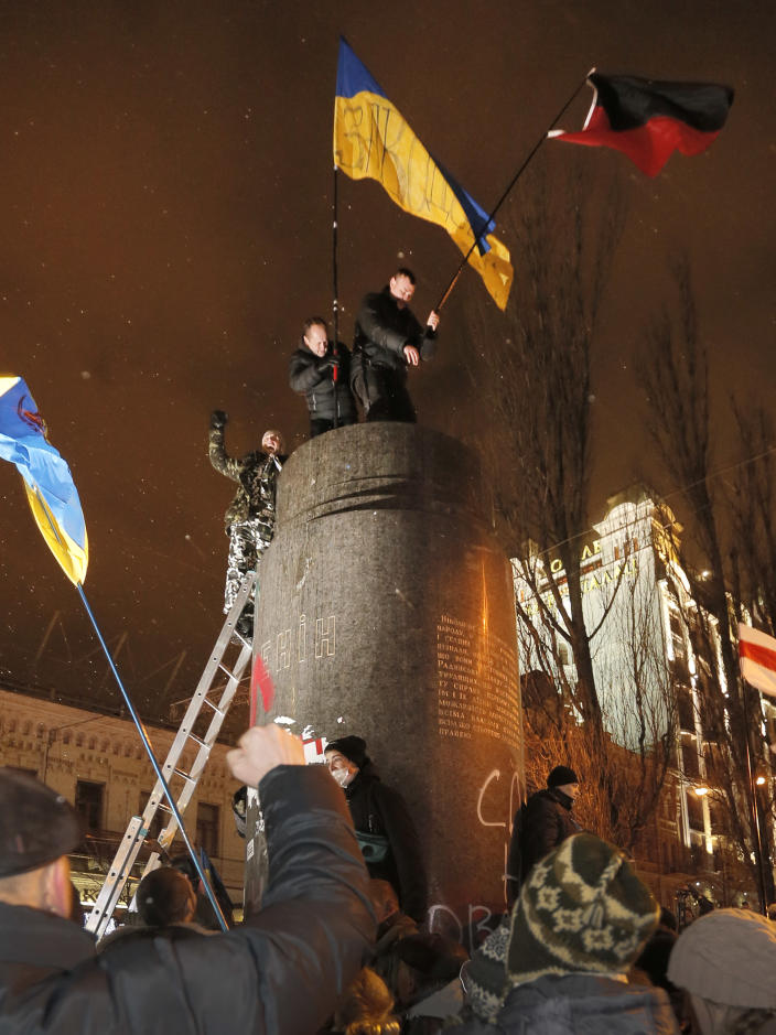 Ukrainian protesters put up Ukrainian flags in place of the ruined monument to Vladimir Lenin in central Kiev, Ukraine, Sunday, Dec. 8, 2013. Anti-government protesters have toppled the statue of Bolshevik leader Vladimir Lenin in central Kiev amid huge protests gripping Ukraine. A group of protesters dragged down and decapitated the landmark statue Sunday evening after hundreds of thousands of others took to the streets to denounce the government's move away from Europe and toward Moscow. (AP Photo/Efrem Lukatsky)