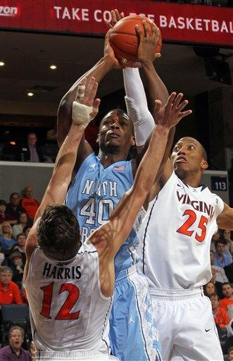 North Carolina forward Harrison Barnes (40) is defended by Virginia guard Joe Harris (12) and forward Akil Mitchell (25) while shooting the ball during the first half of an NCAA college basketball game on Saturday, Feb. 25, 2012, in Charlottesville, Va. (AP Photo/Andrew Shurtleff)