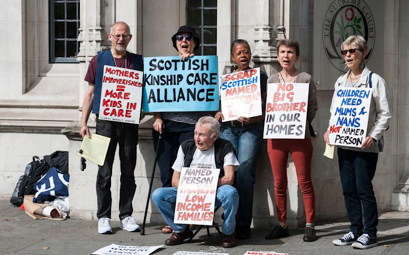 Protestors standing outside the Supreme Court in London last year demonstrating against the Scottish government's Named Person scheme  - Credit: PA