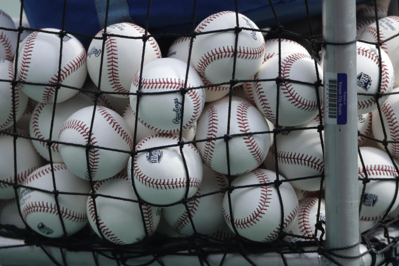 Balls marked with Cactus League spring training logos are seen in a basket during Kansas City Royals baseball practice at Kauffman Stadium Friday, July 3, 2020 in Kansas City, Mo. (AP Photo/Charlie Riedel)