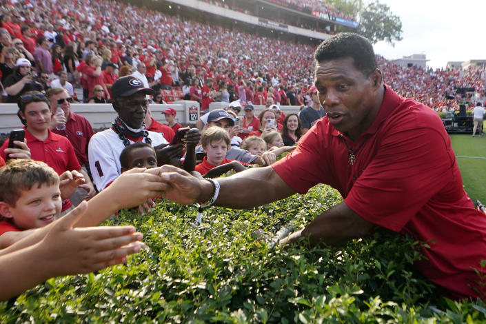 FILE - In this Sept. 11, 2021 file photo, former Georgia running back and Republican candidate for US Senate Herschel Walker greets fans before a college football game between UAB and in Atlanta. The rewards of an early Donald Trump endorsement will be on display Saturday, Sept. 25 in Georgia. A three-man ticket of candidates he's backing in 2022 Republican primaries for statewide office will take the stage with him. (AP Photo/John Bazemore)