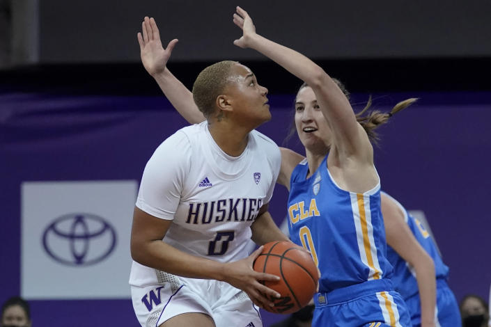 Washington center Quay Miller, left, tries to shoot past UCLA guard Chantel Horvat, right, during the first half of an NCAA college basketball game, Sunday, Feb. 7, 2021, in Seattle. (AP Photo/Ted S. Warren)