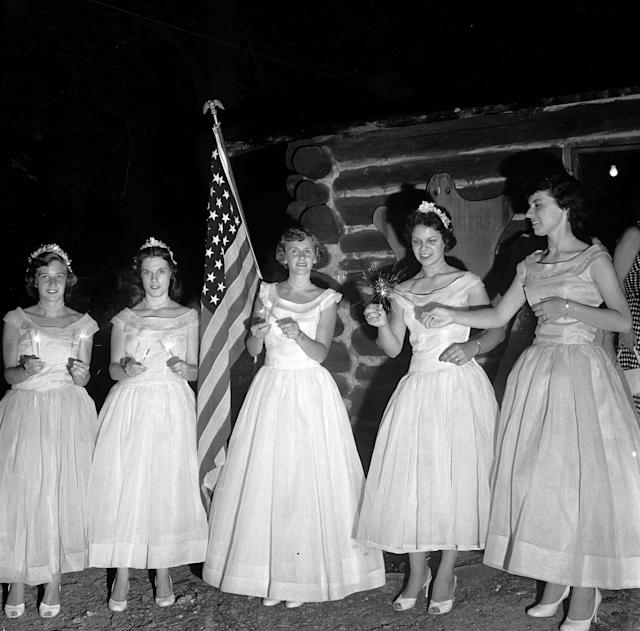 <p>The Queen of Candles and her maids light sparklers before leading the coronation procession, part of the celebrations for the fourth of July, circa 1955. (Photo: Evans/Three Lions/Getty Images) </p>