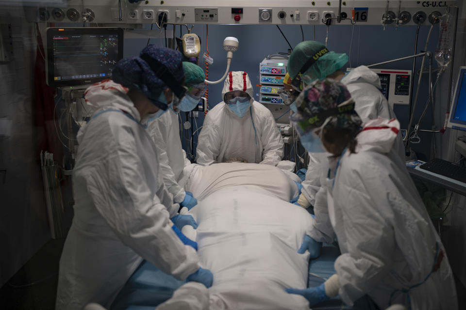 A medical team prepares to rotate a COVID-19 patient in the ICU of the Hospital del Mar, in Barcelona, Spain, Tuesday, Jan. 19, 2021. The unrelenting increase in COVID-19 infections in Spain following the holiday season is again straining hospitals, threatening the mental health of doctors and nurses who have been at the forefront of the pandemic for nearly a year. (AP Photo/Felipe Dana)
