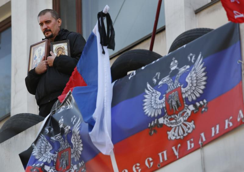 A pro-Russian protester holds icons as he stands outside a city hall bearing flags representing the Donetsk Republic in Mariupol, Ukraine, Thursday, April 17, 2014. Three pro-Russian protesters were killed and 13 injured during an attempted raid overnight on a Ukrainian National Guard base in the Black Sea port of Mariupol, Ukraine's authorities said Wednesday. (AP Photo/Sergei Grits)