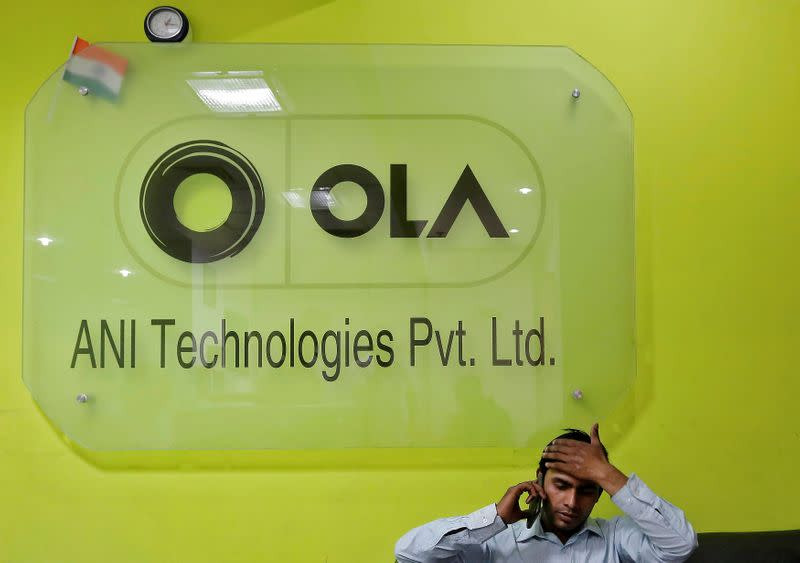 An employee speaks over his phone as he sits at the front desk inside the office of Ola cab service in Gurugram