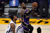 Los Angeles Lakers forward LeBron James, right, goes to the basket as Memphis Grizzlies center Xavier Tillman defends during the first half of an NBA basketball game Friday, Feb. 12, 2021, in Los Angeles. (AP Photo/Mark J. Terrill)