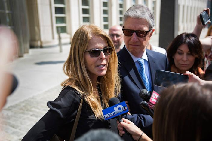 Actress Catherine Oxenberg, left, with Stanley Zareff and Toni Natalie, talks to the press following the arraignment of NXIVM leader Keith Raniere in federal court on Friday, April 13, 2018, in New York.