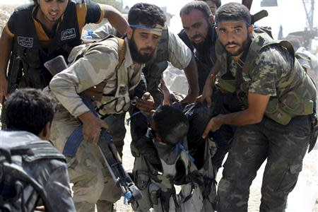 Free Syrian Army fighters carry their fellow fighter after he was wounded on the front line in Aleppo's Sheikh Saeed neighbourhood September 21, 2013. REUTERS/Molhem Barakat