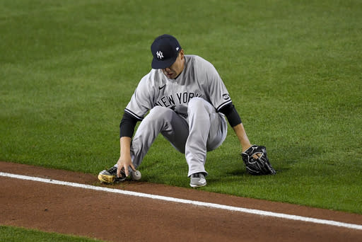 New York Yankees starting pitcher Masahiro Tanaka slips as he reaches for a soft grounder by Toronto Blue Jays' Lourdes Gurriel Jr., who was safe at first during the third inning of a baseball game in Buffalo, N.Y., Wednesday, Sept. 23, 2020. (AP Photo/Adrian Kraus)