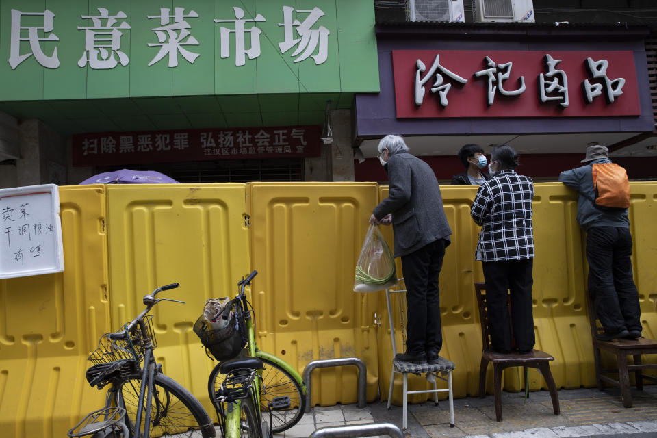 FILE - In this April 3, 2020, file photo, residents climb onto chairs to buy groceries from vendors behind barriers used to seal off a neighborhood in Wuhan in central China's Hubei province. The Chinese city of Wuhan is looking back on a year since it was placed under a 76-day lockdown beginning Jan. 23, 2020. (AP Photo/Ng Han Guan, File)