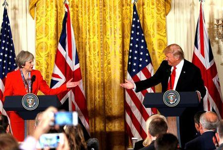 FILE PHOTO: British Prime Minister Theresa May and U.S. President Donald Trump gesture towards each other during their joint news conference at the White House in Washington, U.S., January 27, 2017.   REUTERS/Kevin Lamarque