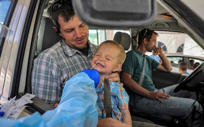 A medic performs a COVID-19 coronavirus swab test on a child in a vehicle at a Home Front command drive-through coronavirus testing complex in Jerusalem - MENAHEM KAHANA/AFP