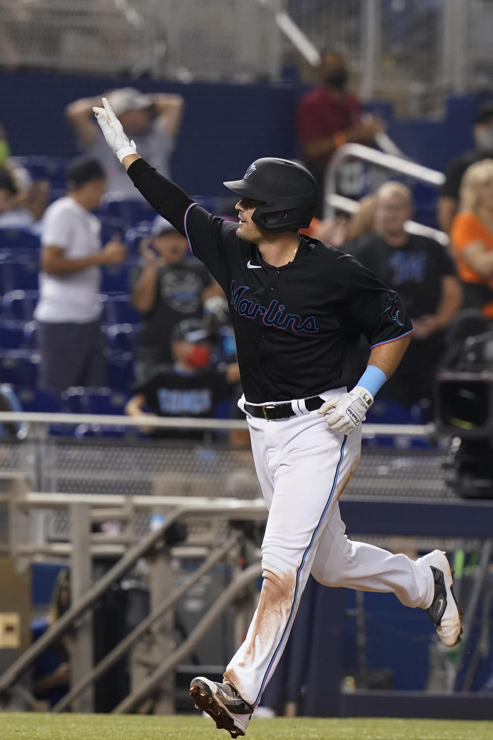 Miami Marlins Nick Fortes raises his hand to the crowd after hitting a two-run home run during the fifth inning of the team's baseball game against the Pittsburgh Pirates, Saturday, Sept. 18, 2021, in Miami. (AP Photo/Marta Lavandier)