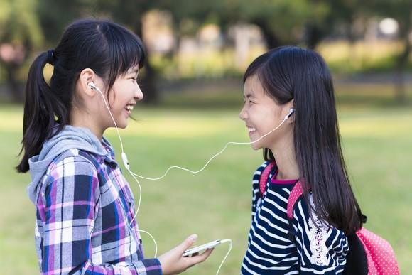 Two Asian girls listening to music on earbuds