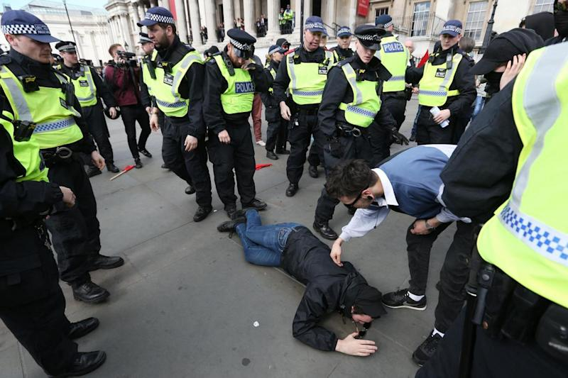 Trouble: A demonstrator falls to the ground in front of police (PA)