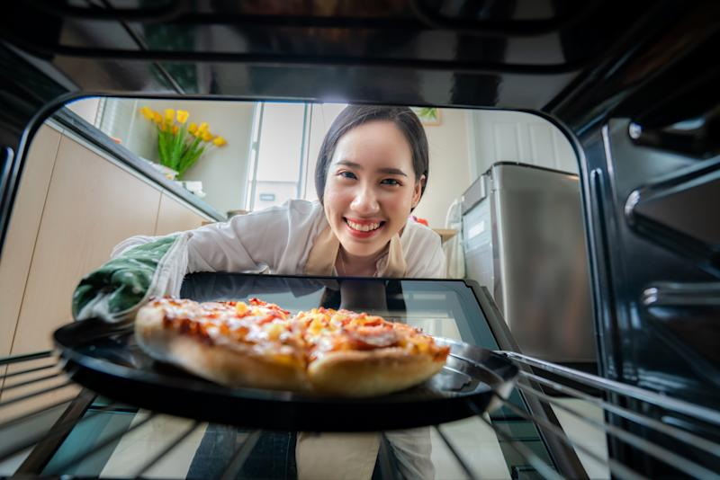 Happy Young Asian Woman looking at camera while cooking and put Pizza in Oven at kitchen at Home . Italian food, cooking, and people lifestyle concept.