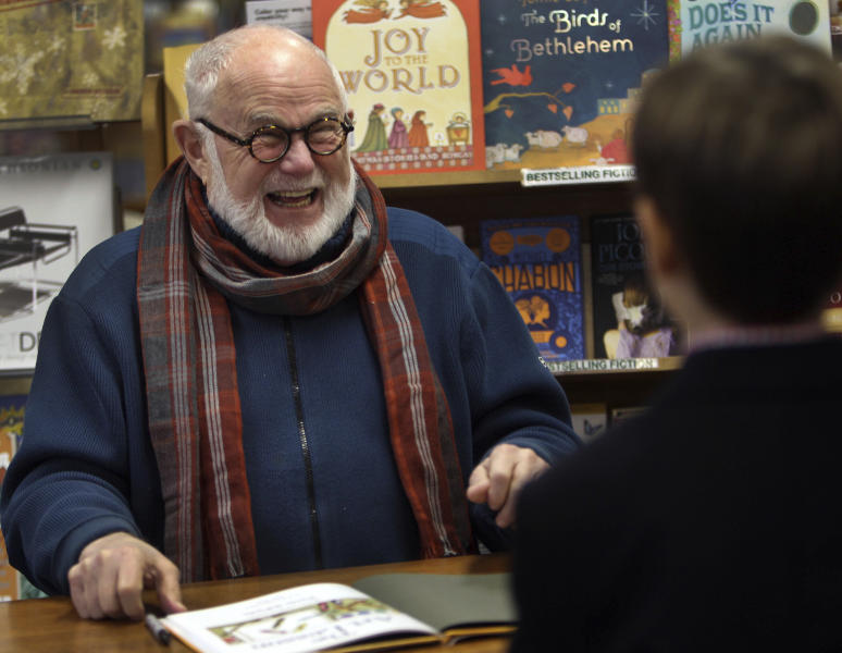 In this photo taken Sunday Dec. 1, 2013, Tomie dePaola laughs as he signs books at the Morgan Hill Bookstore in New London, N.H. The beloved children's author and illustrator has died at the age of 85. DePaola delighted generations with tales of Strega Nona, the kindly and helpful old witch in Italy. His literary agent says dePaola died Monday from surgery complications after taking a bad fall last week. (AP Photo/Jim Cole, File)