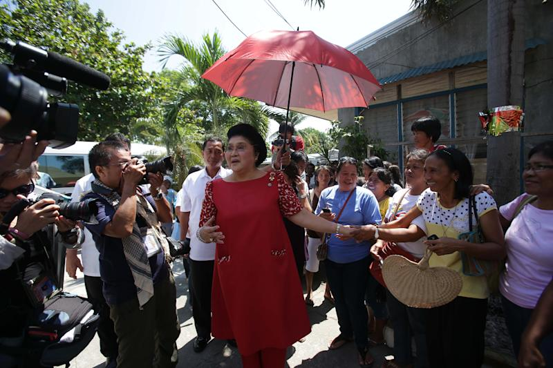 In this May 5, 2013 photo, former Philippine First Lady Imelda Marcos, center, greets supporters during an electoral campaign in Ilocos Norte province, northern Philippines. Twenty-seven years after her dictator husband was ousted by a public revolt, Imelda Marcos has emerged as the Philippines' ultimate political survivor: She was back on the campaign trail this week, dazzling voters with her bouffant hairstyle, oversized jewelry and big talk in a bid to keep her seat in Congress. (AP Photo/Aaron Favila)