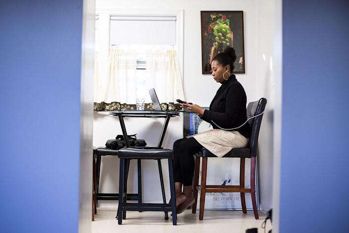 Mona Pompilus works in her kitchen in Foxborough. After a long day of visiting clients for her employer, she often records her notes at home. (Photo: Kayana Szymczak for Yahoo News)