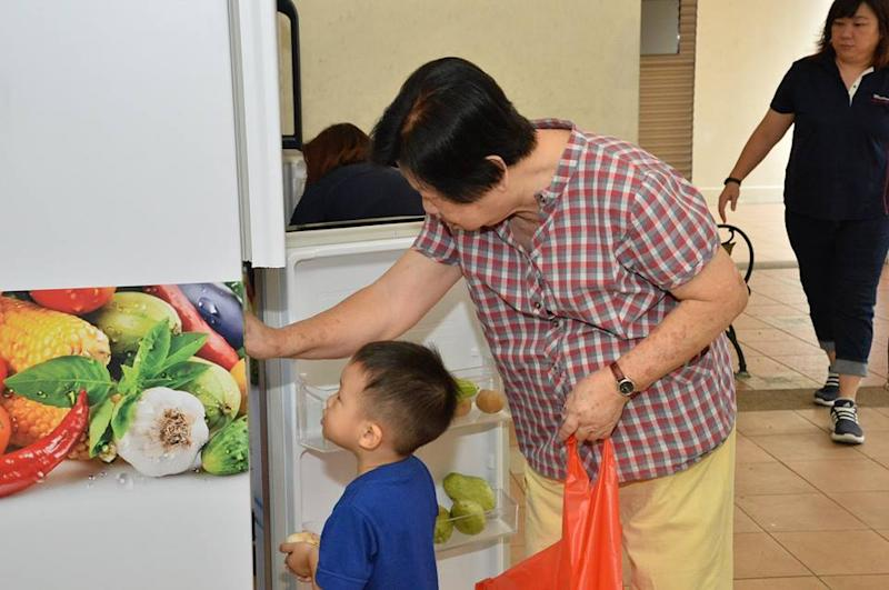 Dorset Road residents -- young and old -- taking items from the community fridges launched in their district (Photo: Melvin Yong / Facebook)