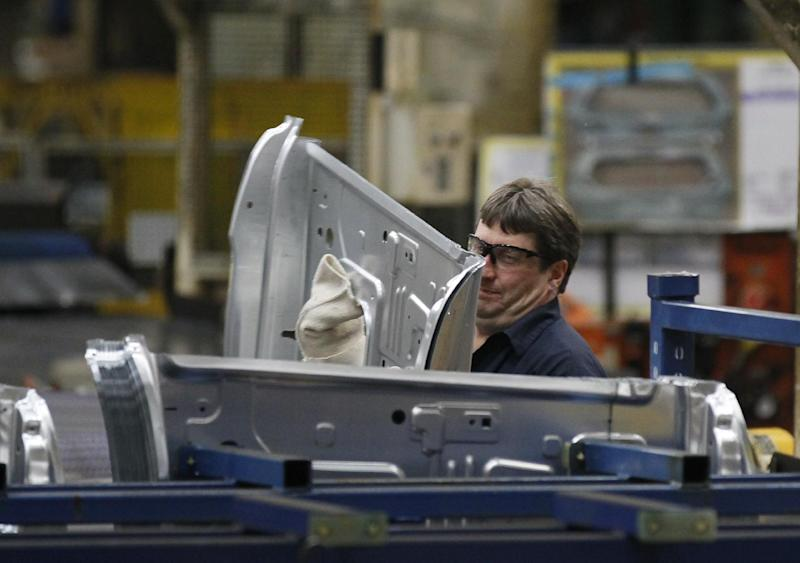In this April 4, 2012, photo, an auto worker at the Ford Stamping Plant in Chicago Heights, Ill. Plummeting sales in Europe, and no hope for a quick fix in the troubled region, hurt Ford's second-quarter profit and forced the company to lower its full-year earnings forecast Wednesday, July 25, 2012. (AP Photo/Charles Rex Arbogast)