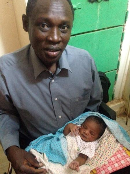 A picture taken on May 28, 2014 and released by the family on May 30 shows Daniel Wani, a US citizen originally from South Sudan, carrying his newborn daughter Maya at the women's prison in Khartoum's twin city of Omdurman (AFP Photo/)