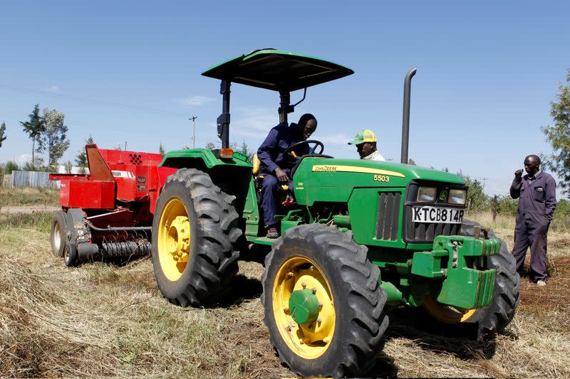 David Kayi, a Hello Tractor engineer, installs an application on a John Deere 5503 tractor, using the Hello Tractor technology that connects farmers with vehicles' owners, at a hay farm in Umande village in Nanyuki