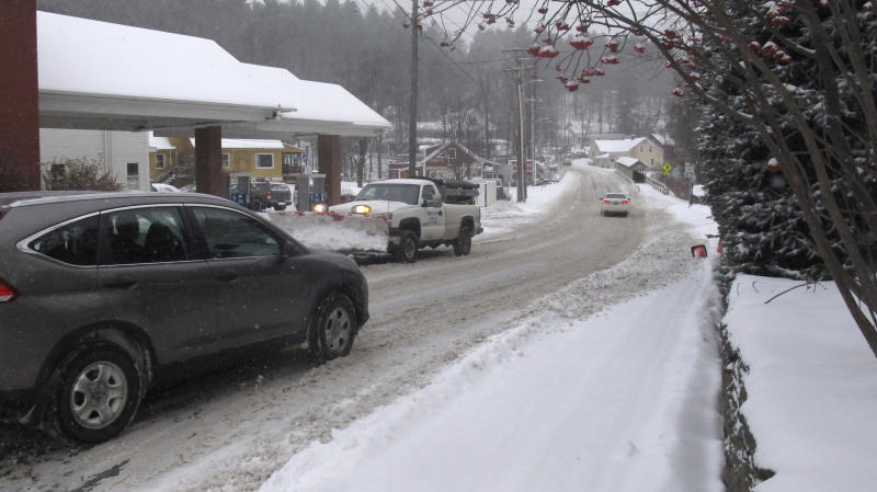 Vehicles make their way on a snow-covered street of Stowe, Vt., on Tuesday, Nov. 12, 2019. In the first significant snow of the season, a wintry mix swept into northern New England, with hundreds of schools closed or delayed in Vermont due to snow, and slick conditions in New Hampshire and Maine. The National Weather Service says record cold could follow the snow. (AP Photo/Wilson Ring)
