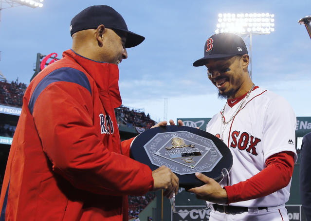 FILE - In this April 11, 2019, file photo, Boston Red Sox manager Alex Cora, left, presents right fielder Mookie Betts with the 2018 AL MVP Award before a baseball game between the Red Sox and the Toronto Blue Jays at Fenway Park in Boston. The award includes the name and image of Kenesaw Mountain Landis. (AP Photo/Winslow Townson, File)