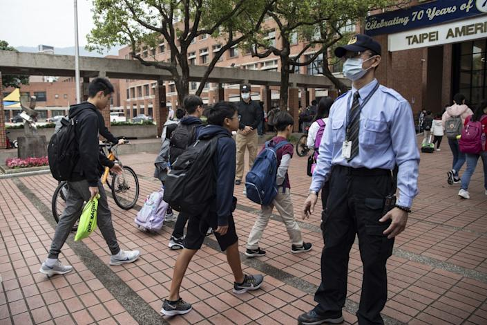 Students enter Taipei American School in Taiwan on Wednesday.
