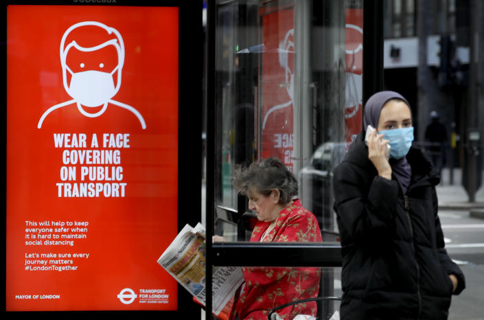 Passengers wait at a bus stop with a sign advising travellers to wear a face covering whilst travelling, in London, Friday, June 5, 2020. It will become compulsory to wear face coverings whilst using public transport in England from Monday June 15. (AP Photo/Kirsty Wigglesworth)