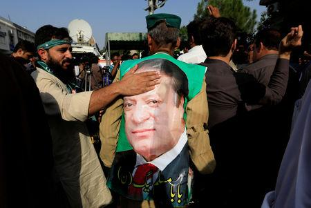 A supporter of former Prime Minister Nawaz Sharif touches his picture as he celebrate with others following the court's decision in Islamabad, Pakistan September 19, 2018.  REUTERS/Faisal Mahmood
