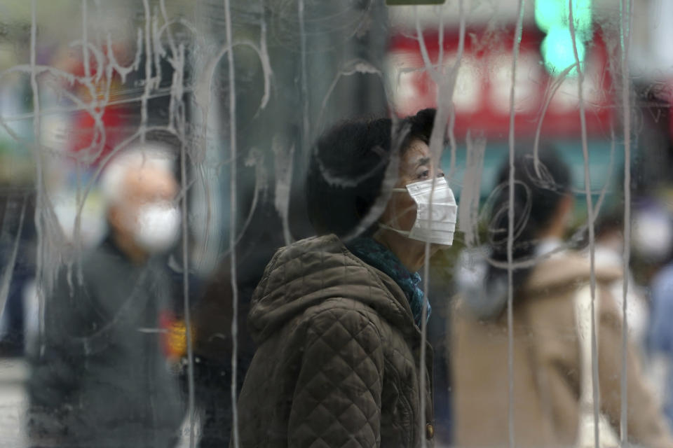 A woman wearing a protective mask to help curb the spread of the coronavirus stands is seen though a scribbled glass window as she walks along pedestrian crossings in the Shibuya area of Tokyo Tuesday, Jan. 5, 2021. Japanese Prime Minister Yoshihide Suga says vaccine approval is being speeded up to curb the spread of the coronavirus, and he promised to consider declaring a state of emergency. The Japanese capital confirmed more than 1200 new coronavirus cases on Tuesday. (AP Photo/Eugene Hoshiko)