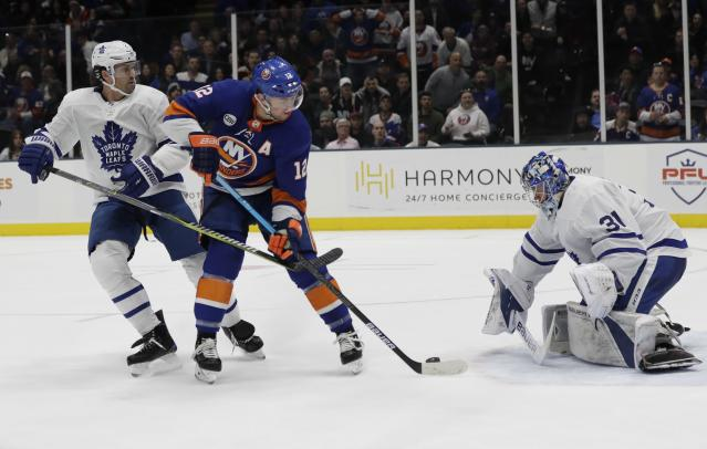 Toronto Maple Leafs goaltender Frederik Andersen (31) stops a shot on the goal by New York Islanders' Josh Bailey (12) as teammate Ron Hainsey (2) watches during the second period of an NHL hockey game Monday, April 1, 2019, in Uniondale, N.Y. (AP Photo/Frank Franklin II)