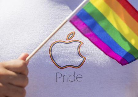 An Apple employee waves a rainbow flag before the San Francisco Gay Pride Festival in California