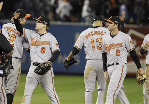 Baltimore Orioles' Nate McLouth (9) and J.J. Hardy (2) celebrate with teammates after Game 4 of the American League division baseball series against the New York Yankees late Thursday, Oct. 11, 2012, in New York. The Orioles won 2-1. (AP Photo/Kathy Willens)