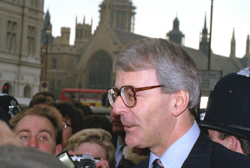 FILE - In this Thursday, Nov. 22, 1990, file photo, Britain's then Treasury chief John Major outside Parliament after he announced he would stand to replace Margaret Thatcher as prime minister. He won and sought to mend fences with the then European Community while still negotiating an opt-out to keep Britain out of the euro single currency. On Jan. 31, 2020, Britain is scheduled to leave what became known as the European Union after 47 years of membership. (AP Photo/Robin Nowacki, File)