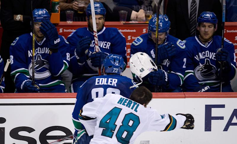 San Jose Sharks' Tomas Hertl (48), of the Czech Republic, loses his helmet as he collides with Vancouver Canucks' Alexander Edler, of Sweden, during the second period of an NHL hockey game in Vancouver, British Columbia, Thursday, Oct. 10, 2013. (AP Photo/The Canadian Press, Darryl Dyck)
