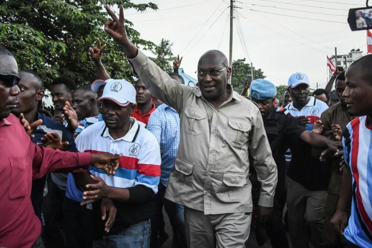 Mbowe, waving, was detained with 15 other party members in a late-night crackdown last week