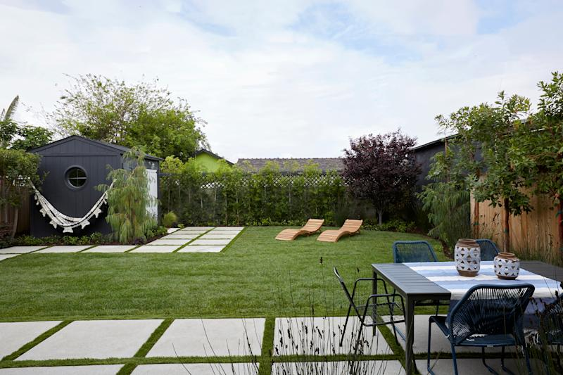 """AFTER: Artificial turf and new grasses were added, as well as custom pathways around the yards. The pathway continues to the front of the decking and """"she shed"""" and can be used as a space for alfresco dining."""