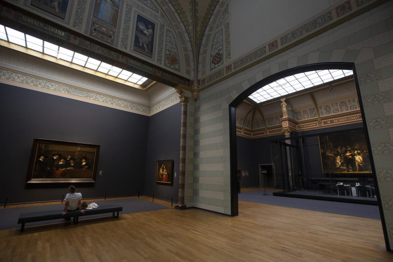 A limited amount of visitors admire paintings and Rembrandt's Night Watch, right, at the reopened Rijksmuseum in Amsterdam, Netherlands, Monday, June 1, 2020. The Dutch government took a major step to relax the coronavirus lockdown, with bars, restaurants, cinemas and museums reopening under strict conditions. (AP Photo/Peter Dejong)