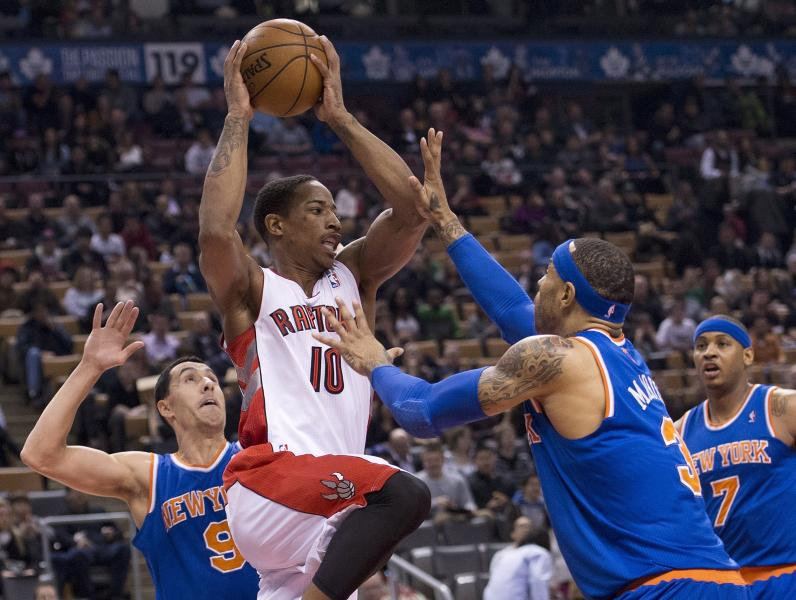 Toronto Raptors forward DeMar DeRozan, center, protects the ball from New York Knicks forwards Kenyon Martin, second right, and Pablo Prigioni, left, during first half NBA basketball action in Toronto on Friday, March 22, 2013. (AP Photo/The Canadian Press, Nathan Denette)