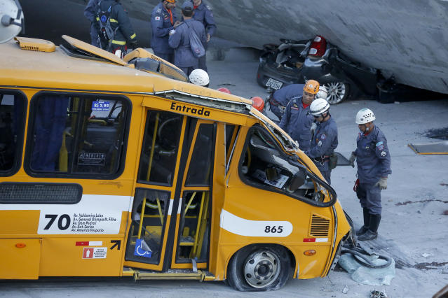 Fire department personnel work to retrieve a body from a bus after retrieving it from underneath a collapsed bridge in Belo Horizonte, Brazil, Thursday, July 3, 2014. The overpass under construction collapsed Thursday in the Brazilian World Cup host city. The incident took place on a main avenue, the expansion of which was part of the World Cup infrastructure plan but, like most urban mobility projects related to the Cup, was not finished on time for the event
