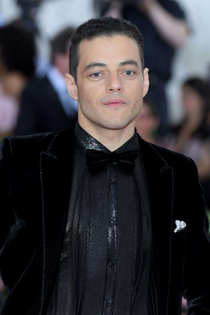 Rami Malek wore Panthère de Cartier brooch, 18k white gold, emeralds, onyx, diamonds and Cartier Tank MC watch, large model, steel, leather. (Photo by Karwai Tang/WireImage )